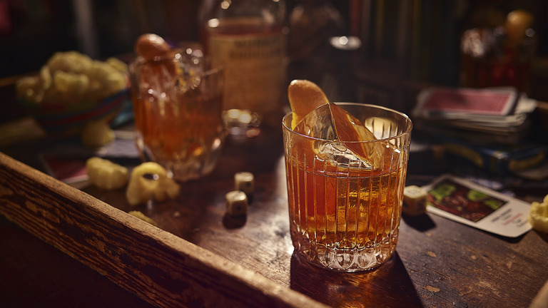 Två glas med drinken Old Fashioned – Monkey Shoulder på en bänkskiva av trä.